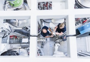 Top view of two colleagues working at industrial robot in modern factory